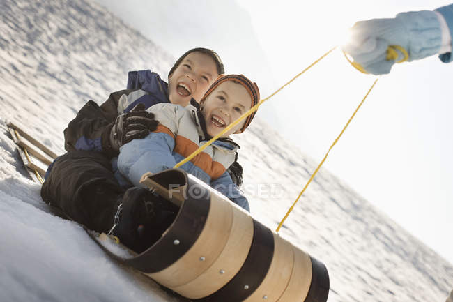 Person pulling two children on a sledge. — Stock Photo