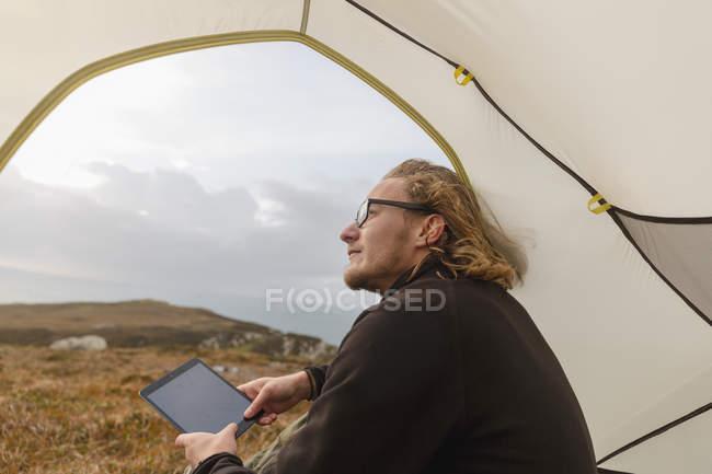 Uomo in tenda che tiene una compressa digitale — Foto stock