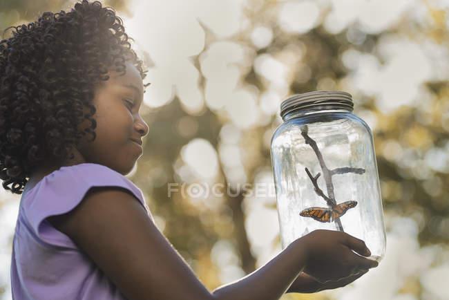 Ragazza in possesso di un vaso di vetro con una farfalla — Foto stock