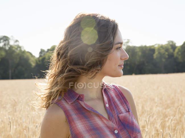 Mujer de pie en un campo de trigo maduro alto - foto de stock