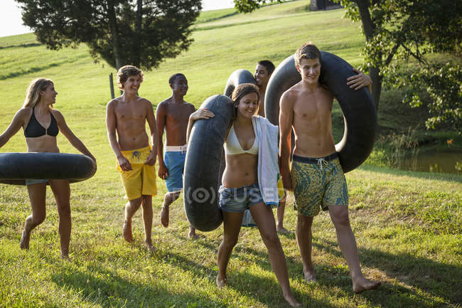Boys and girls, holding towels and swim floats — Stock Photo