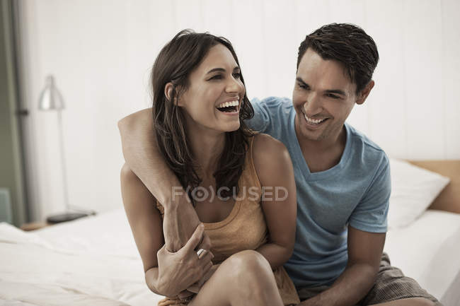 Couple sitting together on the edge of a bed — Stock Photo
