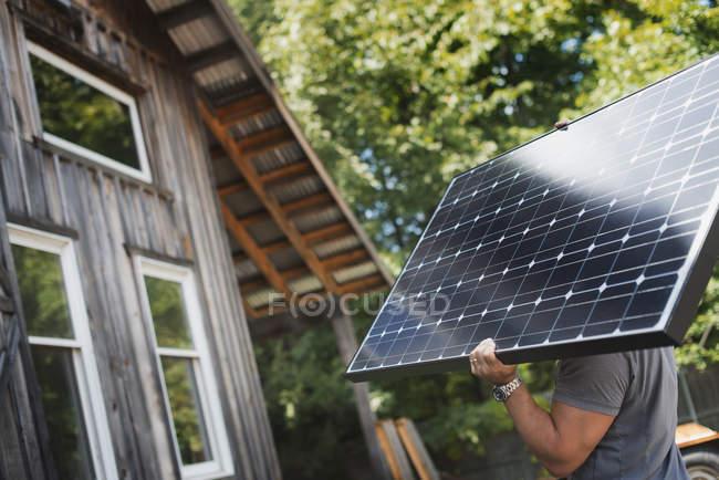 Man carrying a solar panel — Stock Photo