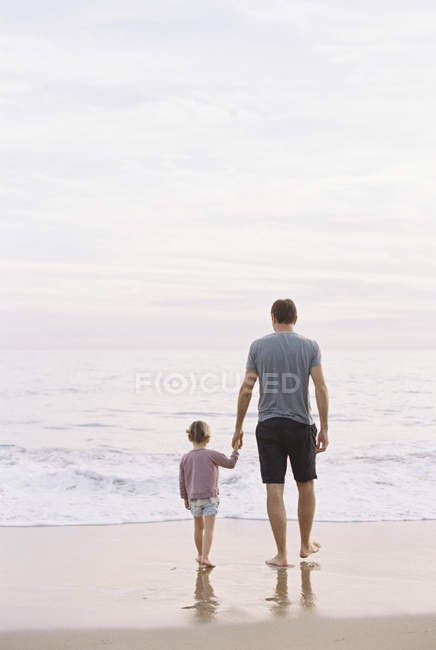 Man with daughter on beach by the ocean — Stock Photo