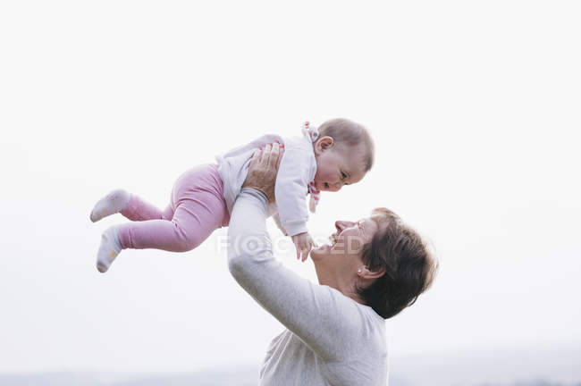 Femme portant un bébé dans l'air — Photo de stock