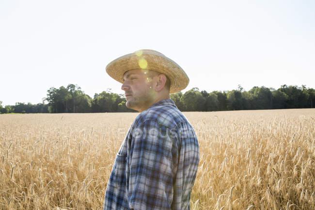 Фермер, стоящий на пшеничном поле — стоковое фото