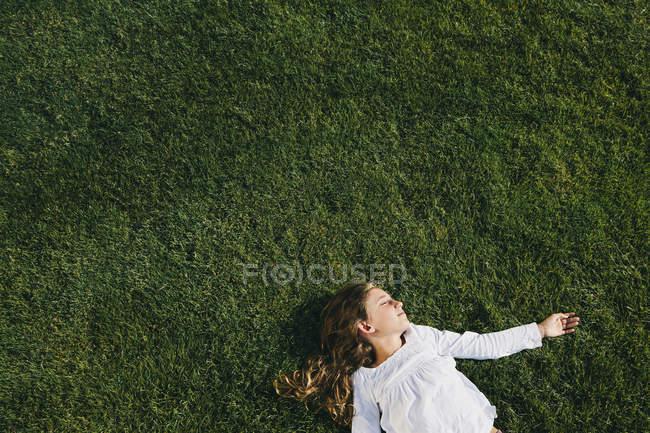 Девятилетняя девочка на зеленой траве — стоковое фото