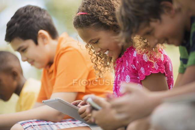 Enfants utilisant des comprimés et des jeux portables . — Photo de stock