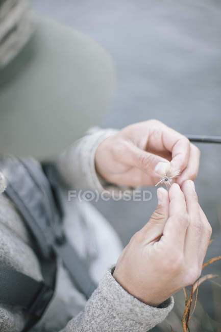 Tying a fishing fly onto a hook . — стоковое фото