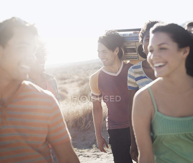 Friends walking on the open road with a boombox. — Stock Photo