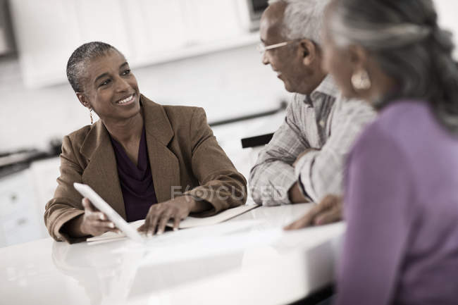 Three people at a table with digital tablet — Stock Photo