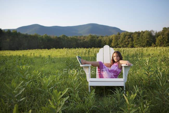 Молодая девушка, сидя в кресле — стоковое фото