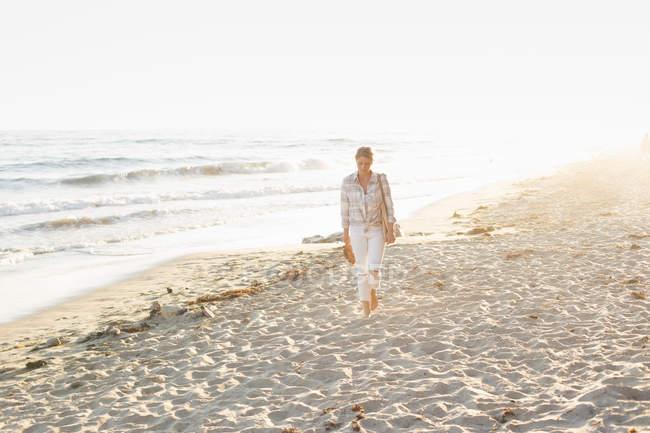 Woman walking along a sandy beach — Stock Photo