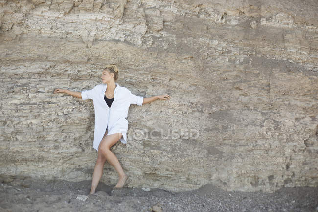 Woman leaning against a cliff — Stock Photo