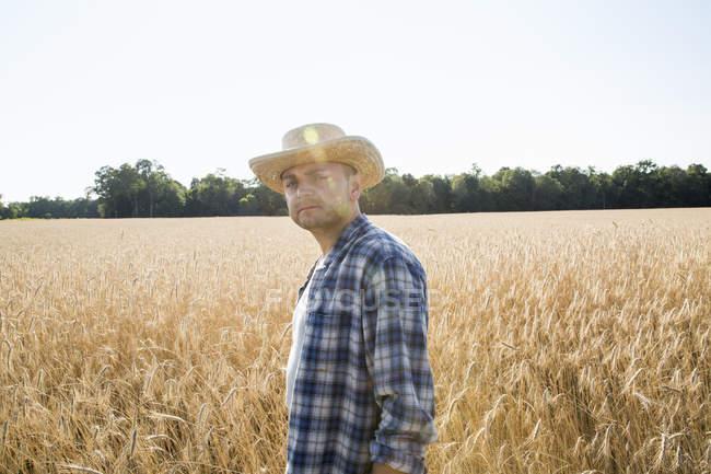 Farmer standing in a wheat field — Stock Photo