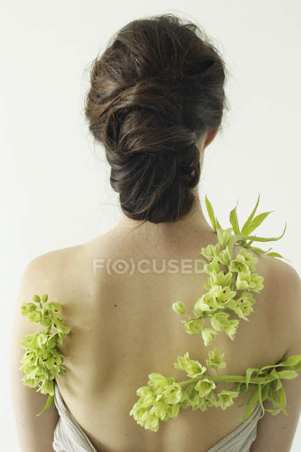 Женщина с зелеными цветами — стоковое фото