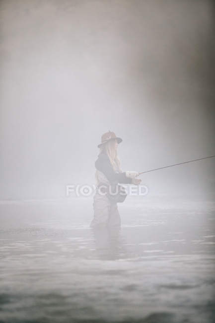 Woman flyfishing in thigh deep water. — Stock Photo