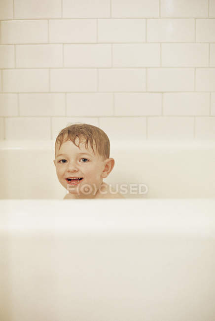 Young boy sitting in a bathtub — Stock Photo