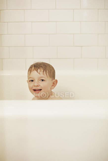 Young boy sitting in a bathtub — Stock Photo