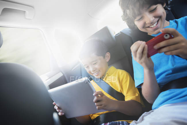 Boys with tablet and smartphone in car — Stock Photo