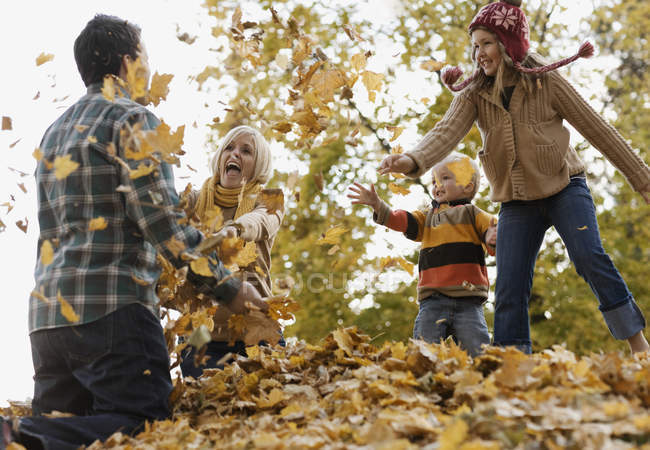 Family playing in autumn leaves. — Stock Photo