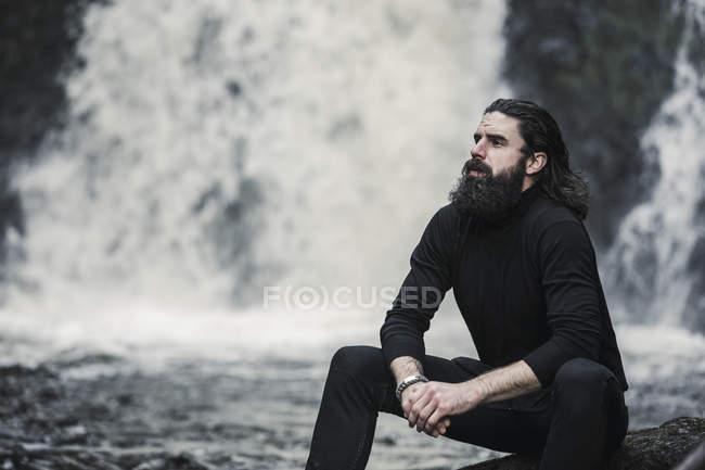 Man sitting at mountain stream. — Stock Photo
