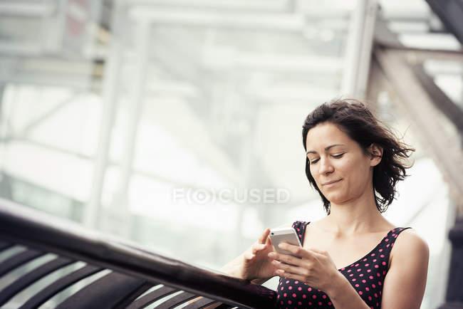 Femme vérifiant son téléphone portable — Photo de stock