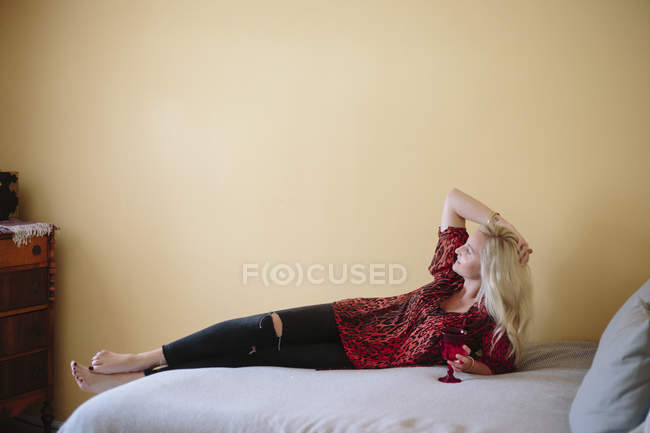 Woman reclining on a bed. — Stock Photo