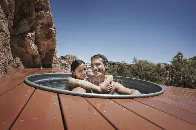 Couple on the terrace in a sunken hot tub. — Stock Photo