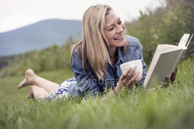 Жінка лежить на траві і читає книжку. — стокове фото