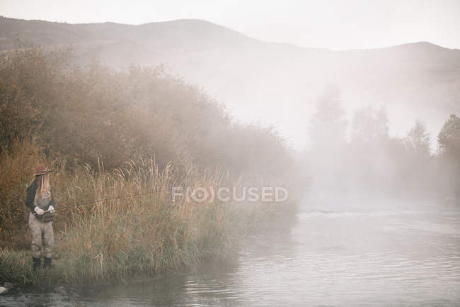 Woman fishing, standing on the riverbank. — Stock Photo