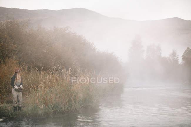 Mulher pesca, de pé na margem do rio . — Fotografia de Stock