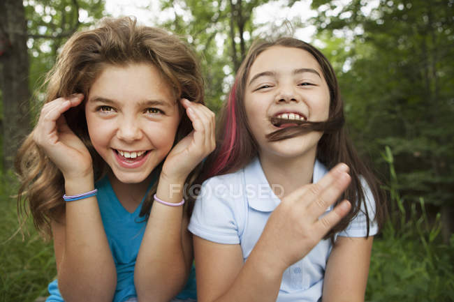Girls sitting side by side and laughing — Stock Photo