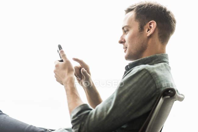Homem sentado verificando seu telefone . — Fotografia de Stock
