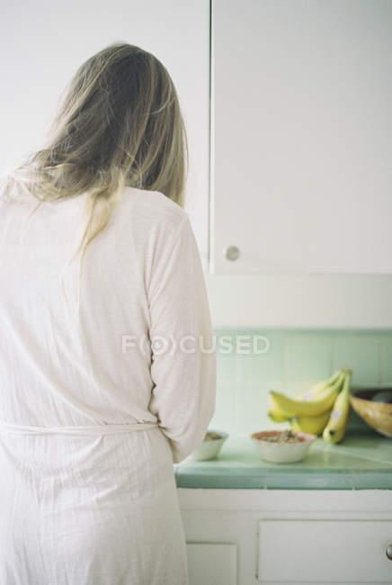 Mulher de pé em uma cozinha — Fotografia de Stock