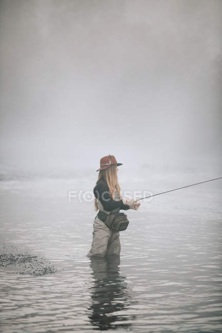 Woman flyfishing in waders in thigh deep water. — Stock Photo