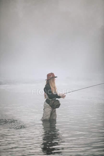 Mulher voando em perneiras na coxa águas profundas . — Fotografia de Stock
