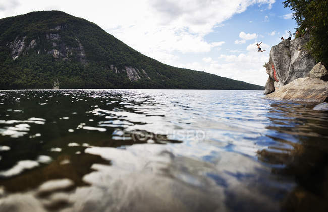 Pessoas a saltar de uma altura de um penhasco — Fotografia de Stock