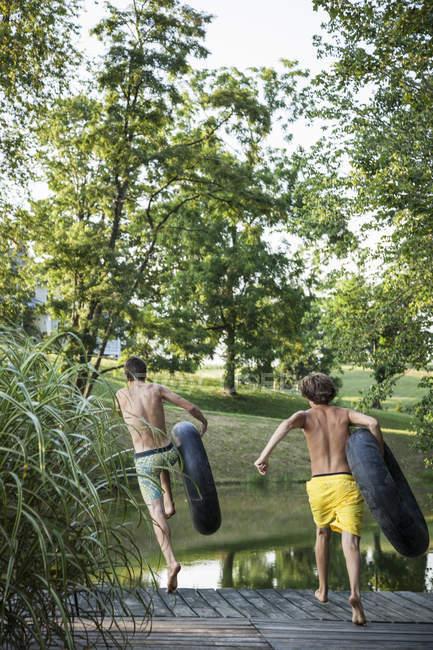 Dois rapazes, pulando do cais em água — Fotografia de Stock