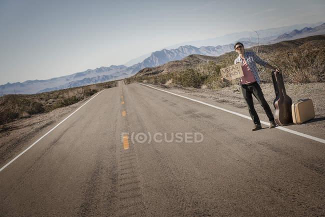 Чоловічий автостопом з гітарою і випадок — стокове фото