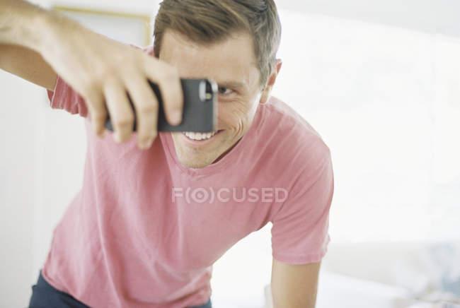 Uomo sorridente che scatta una foto — Foto stock