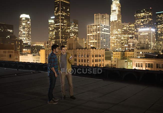 Homens em um telhado olhando para um telefone inteligente . — Fotografia de Stock