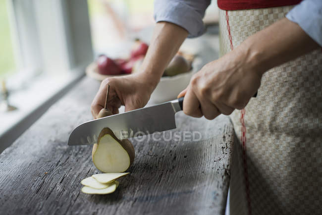 Woman slicing a fresh picked fruit — Stock Photo