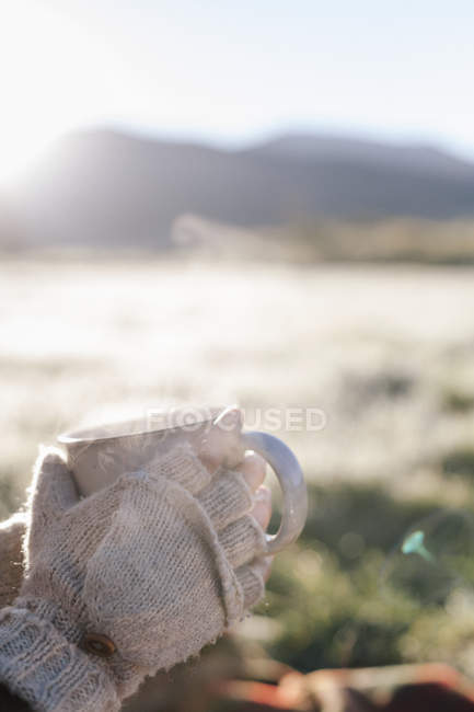 Persona con bebida caliente en sus manos . - foto de stock