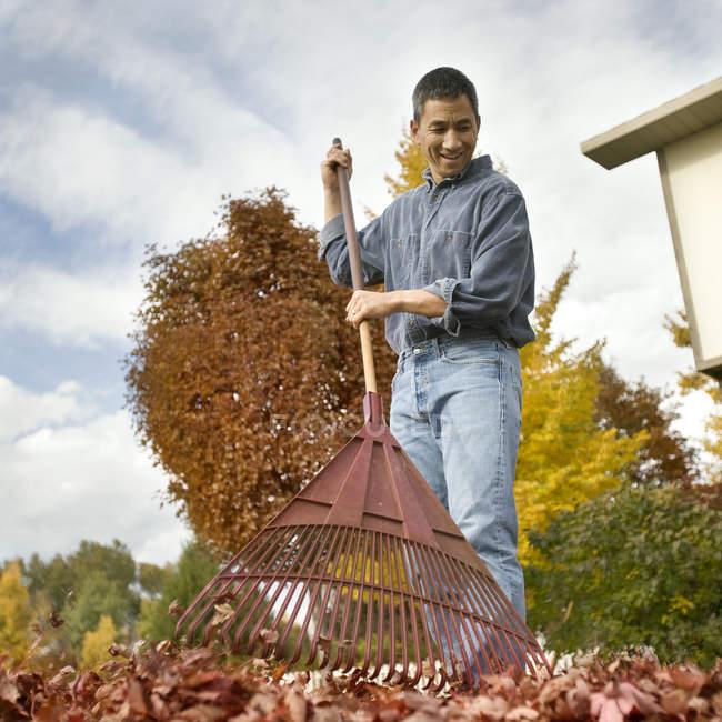 Rechen im Herbst Laub Mann — Stockfoto