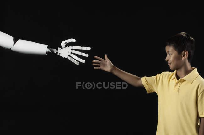 Boy reaching up to robotic hand. — Stock Photo