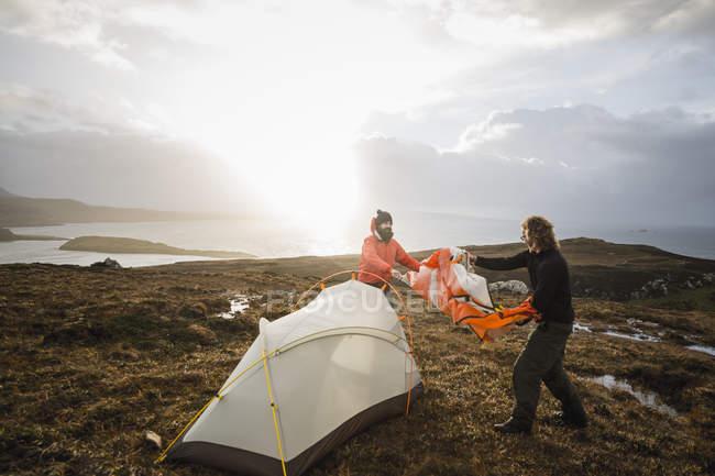 Männer halten und ein kleines Zelt aufstellen — Stockfoto