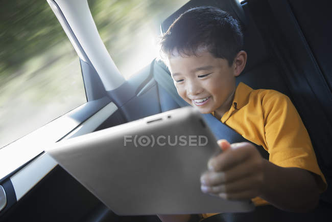 Menino com tablet digital no carro — Fotografia de Stock