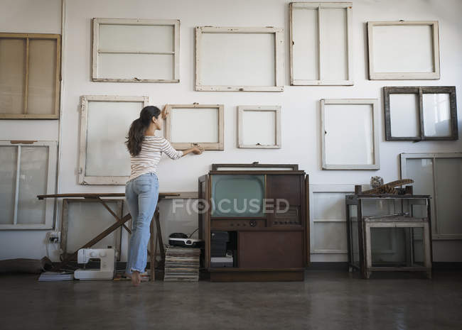 Woman hanging picture frames — Stock Photo