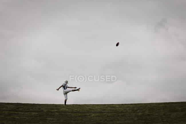 Футболист в форме тренируется пинать мяч. — стоковое фото